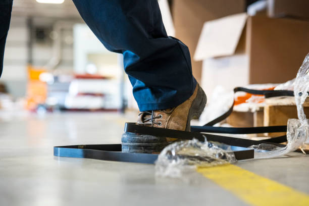An industrial safety topic.  A worker tripping over a trash on a factory floor An industrial safety topic.  A worker in danger of tripping over a piece of metal strapping in a factory. misfortune stock pictures, royalty-free photos & images