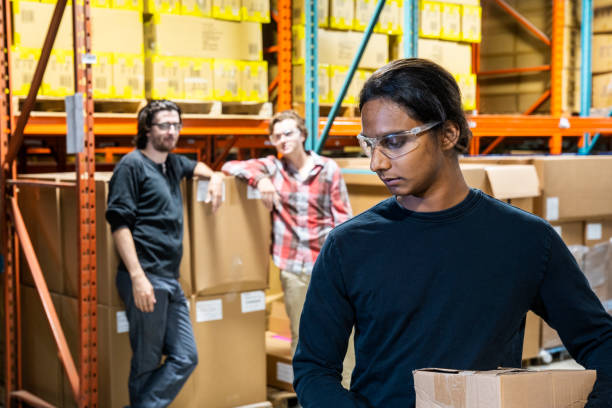 An industrial warehouse worker being the target of bullying stock photo