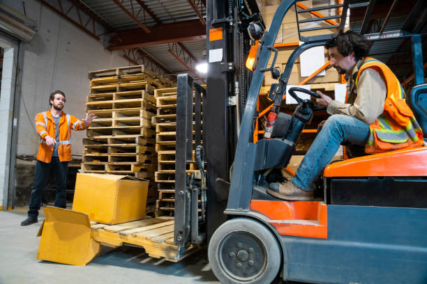 An industrial warehouse workplace safety and asset protection topic.  A forklift driver crashes into and damages merchandise by driving carelessly. An industrial warehouse workplace safety and asset protection topic. A forklift driver damages merchandise by lowering his forks. A coworker informs him of his mistake. pallet jack stock pictures, royalty-free photos & images