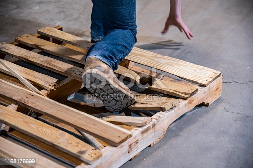 An industrial warehouse, workplace safety topic.  A close-up of a person stepping on a broken pallet that poses a severe risk of causing a fall and injury.