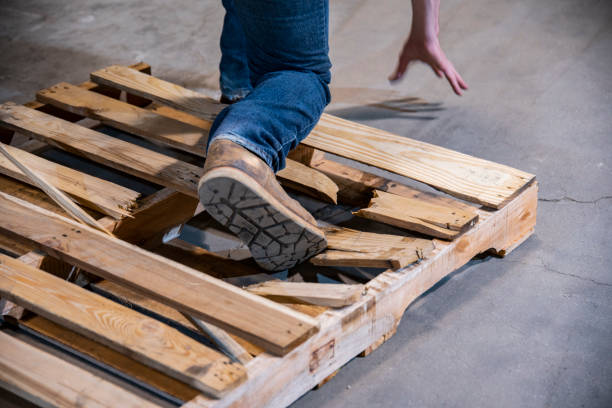 An industrial warehouse, workplace safety topic.  A close-up of a person stepping on a broken pallet. stock photo