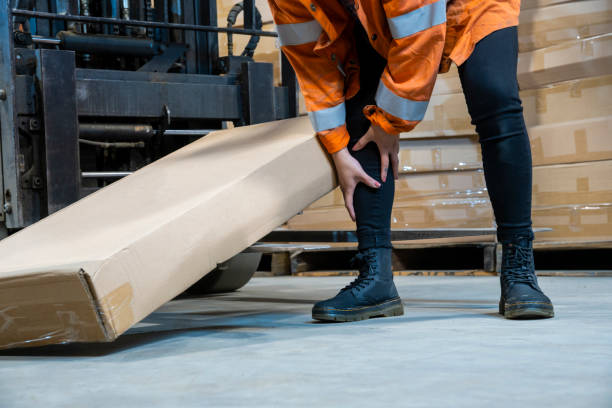 An industrial warehouse workplace safety topic.  A female employee injured by tripping over forklift forks. stock photo