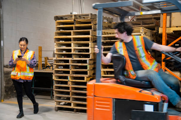 An industrial warehouse workplace safety topic. A female worker distracted by her mobile cell phone as a forklift approaches. stock photo