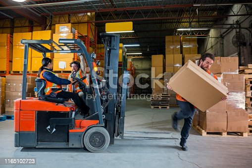 An industrial warehouse workplace safety topic.  A male employee injured by tripping over forklift forks.  Forks must be placed on the ground to avoid being trip hazards.