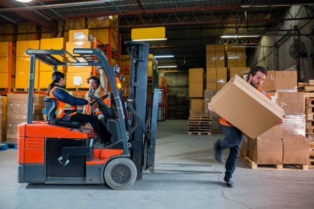 An industrial warehouse workplace safety topic.  A maleemployee injured by tripping over forklift forks. stock photo