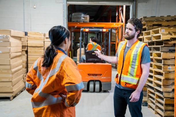 An industrial warehouse workplace safety topic. A manager discusses an issue about a forklift driver. stock photo