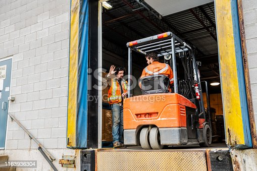 An industrial warehouse workplace safety topic.  A manager or supervisor stops a forklift driver from backing up over a loading dock.  Forklift accidents at loading docks are major contributors to serious injuries in the workplace.