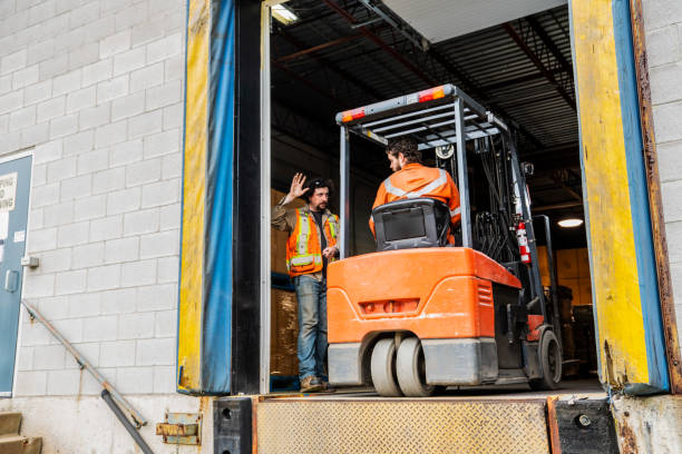 An industrial warehouse workplace safety topic.  A manager or supervisor stops a forklift driver from backing up over a loading dock. stock photo
