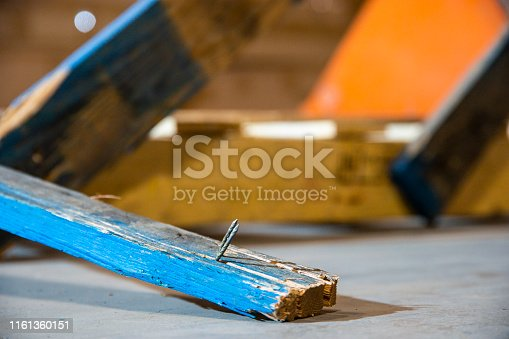 An industrial, warehouse, workplace safety topic.  A nail dangerously protruding from a broken pallet.