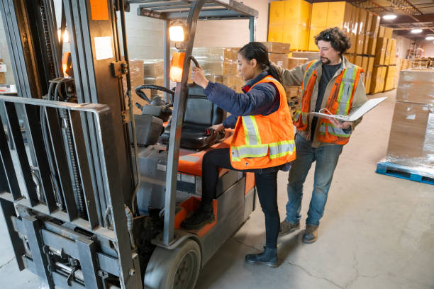 An industrial warehouse workplace safety topic.  A safety supervisor or manager training a new employee on forklift safety. stock photo