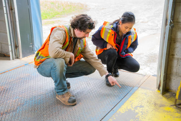 An industrial warehouse workplace safety topic.  A supervisor or manager explains the danger involved with lifting and dropping loading dock plates. stock photo