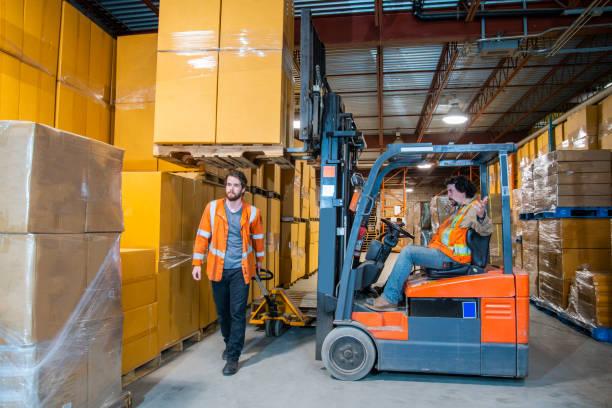 Ein Thema für die Sicherheit am Arbeitsplatz in Industrielagern.  Ein Arbeiter in der Gefahrenzone, der unter einem erhöhten Gabelstapler mit einer Ladung läuft. – Foto