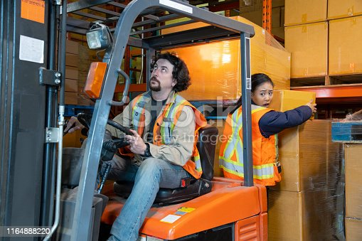 An industrial warehouse workplace safety topic.  A worker in the danger zone. Injuries caused by forklift accidents are a major safety issue.