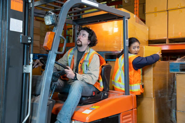 An industrial warehouse workplace safety topic. A worker in the danger zone, working behind a forklift carrying a load. stock photo
