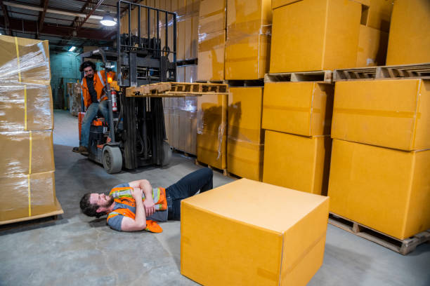 An industrial warehouse workplace safety topic. A worker injured falling or being struck by a forklift. stock photo