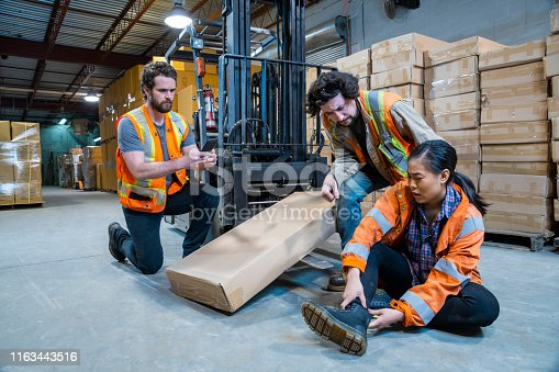 istock An industrial warehouse workplace safety topic. A worker injured falling or being struck by a forklift. 1163443516