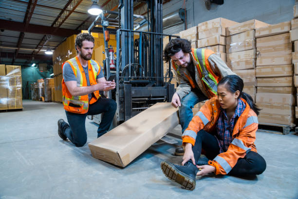 An industrial warehouse workplace safety topic. A worker injured falling or being struck by a forklift. An industrial warehouse workplace safety topic. A worker injured falling or being struck by a forklift. Falls and collisions are major contributors to forklift safety. misfortune stock pictures, royalty-free photos & images