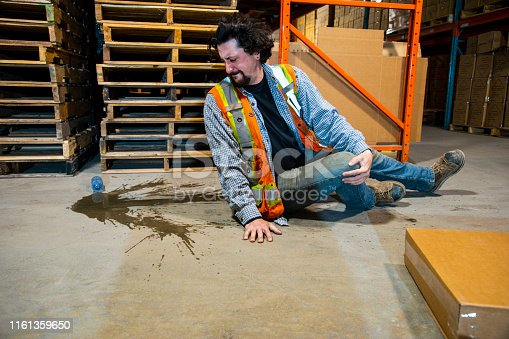 An industrial, warehouse, workplace safety topic.  An employee risks injury by slipping on a plastic water bottle.  Slips, trips and falls are major contributors to safety incidents in distribution centers, and factories.