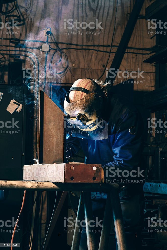 An industrial welder welding iron in workplace stock photo
