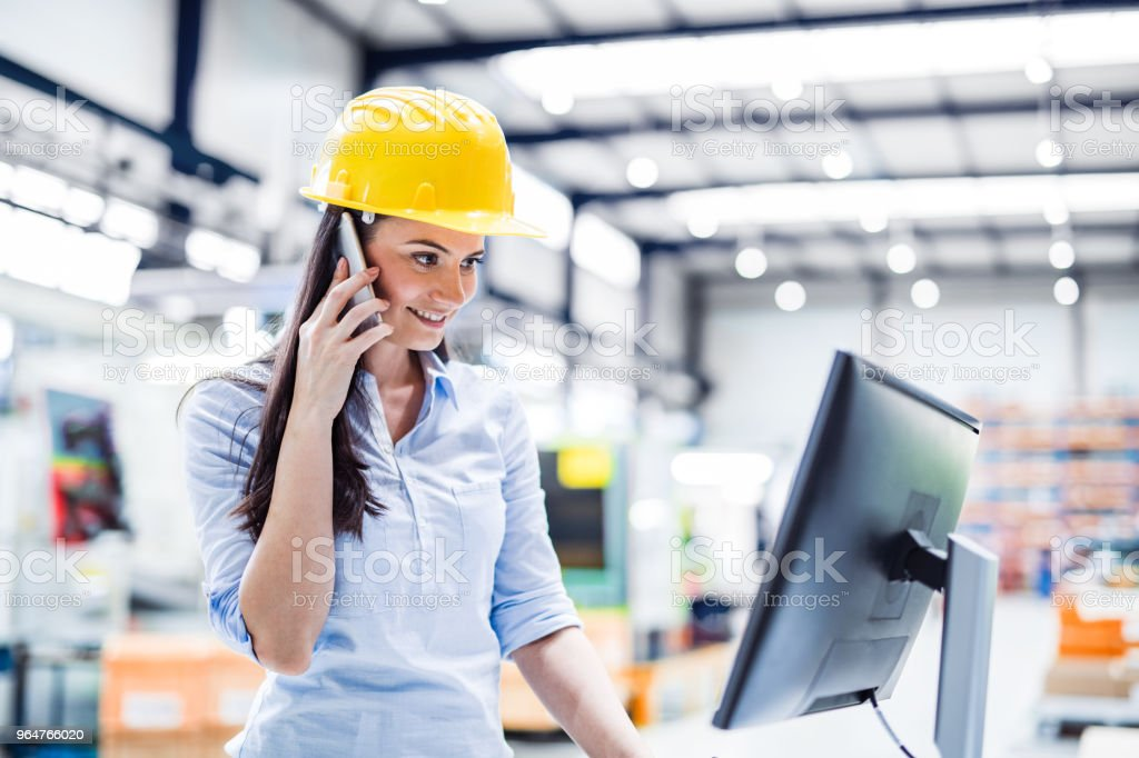 An industrial woman engineer with desktop computer and smartphone in a factory. royalty-free stock photo