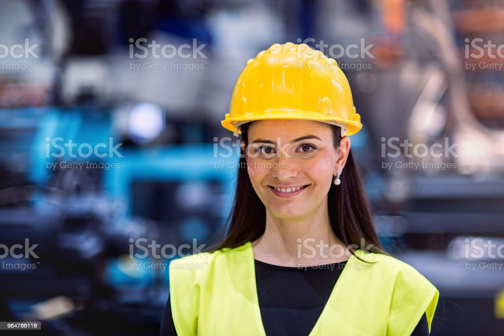 An industrial woman engineer with helmet in a factory. Copy space. royalty-free stock photo