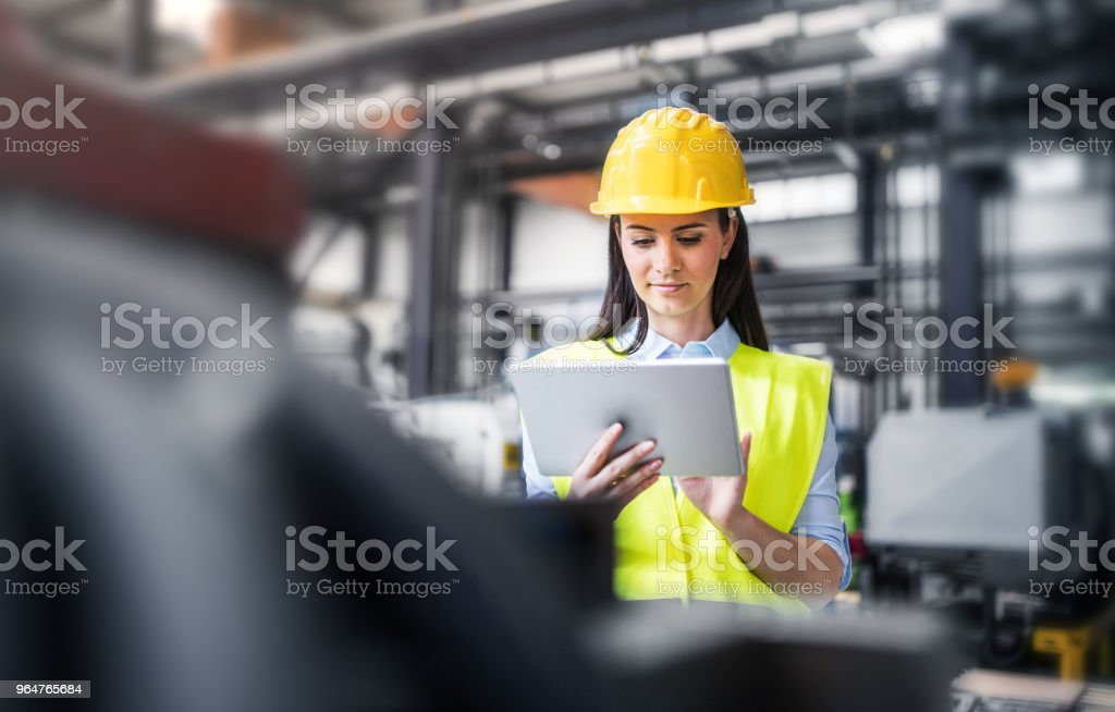 An industrial woman engineer with tablet standing in a factory. royalty-free stock photo