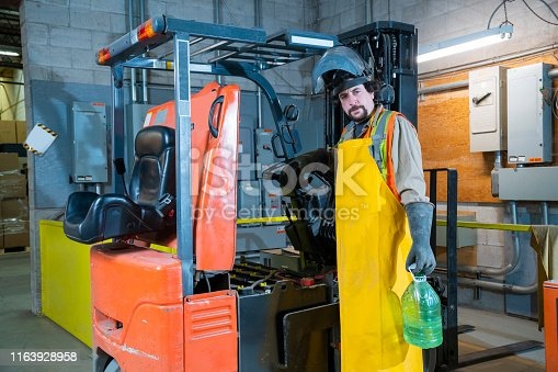 An industrial workplace safety topic.  A man uses the correct PPE to check battery acid levels and service a forklift.