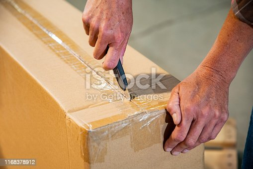 An industrial workplace warehouse safety topic. A female cutting a box using a utility knife.