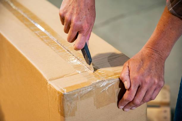 Ein Thema für die Sicherheit von Arbeitslagern. Eine Frau schneidet eine Schachtel mit einem Gebrauchsmesser. – Foto