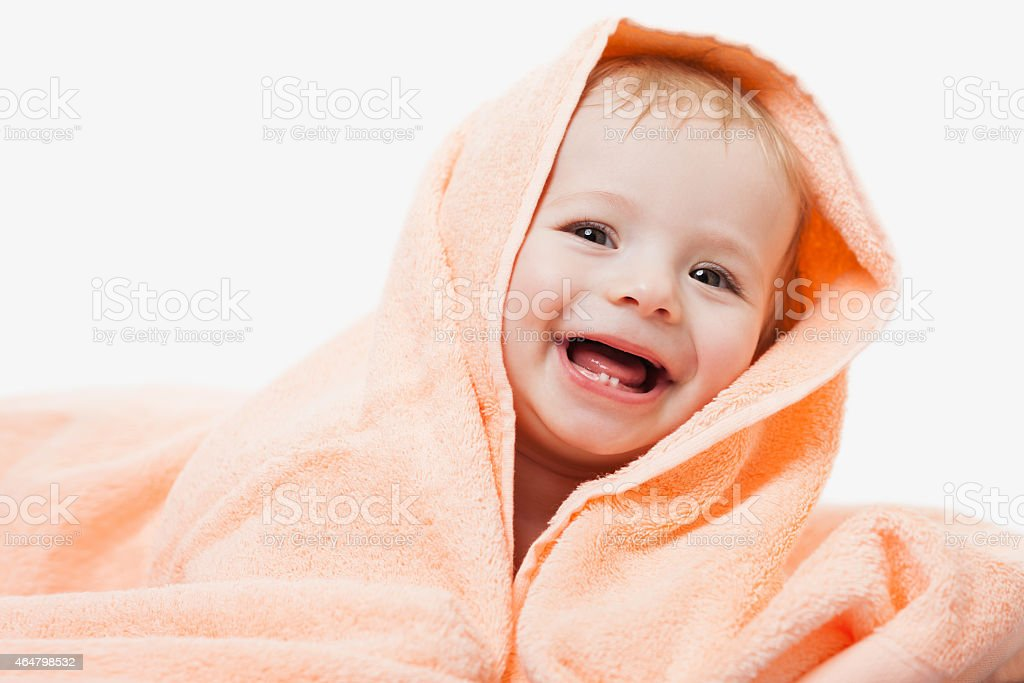 An infant in a peach towel smiling at the camera stock photo