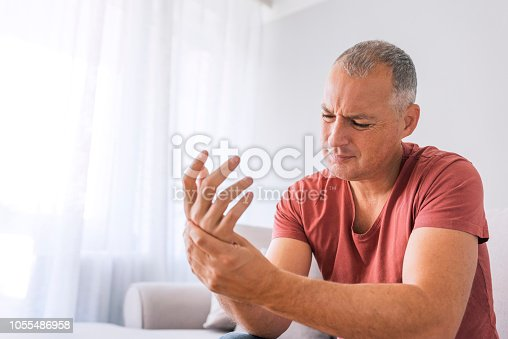 Photo of Mature man suffering from wrist pain at home while sitting on sofa during the day. Clenched painful hands