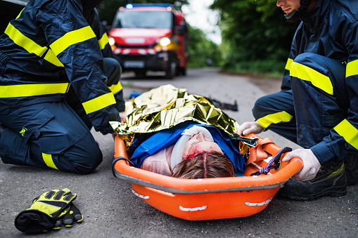 istock An injured woman in a plastic stretcher after a car accident, covered by thermal blanket. 1047076382
