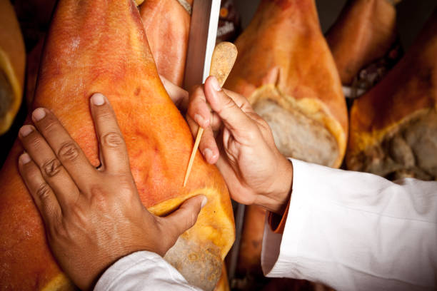 An inspector checking drying Parma ham stock photo
