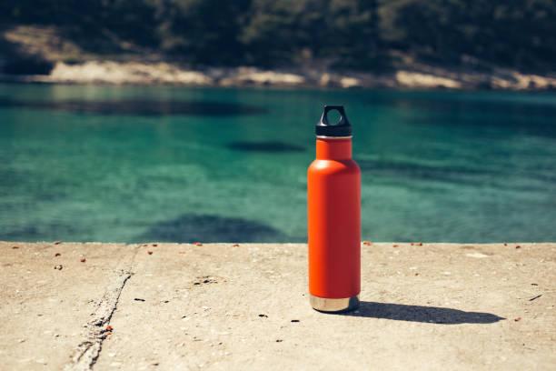 uma garrafa de água alaranjada isolada na praia - sports water bottle - fotografias e filmes do acervo