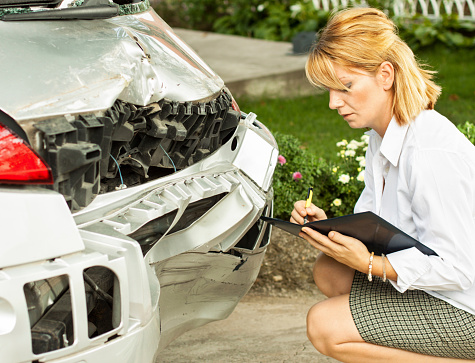 An Insurance Adjuster Looking At The Damaged Bumper Of A ...