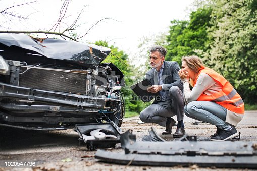 istock An insurance agent and a woman driver looking at the car on the road after an accident. 1020547796