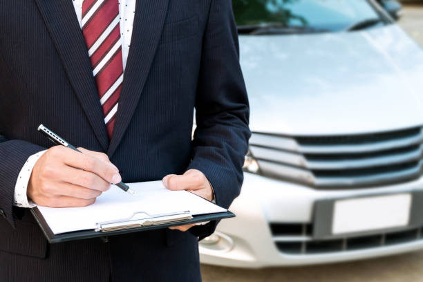 An insurance expert employee working with a car at the outdoor stock photo