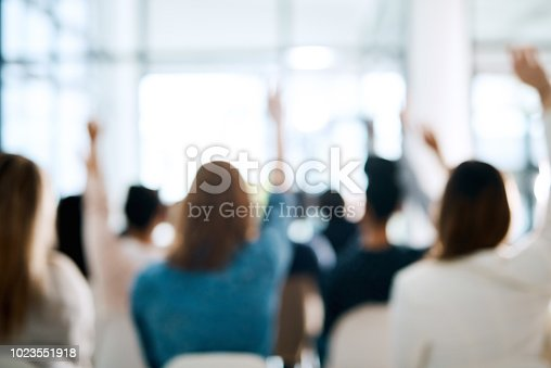Rearview shot of a group of businesspeople raising their hands to ask questions during a conference