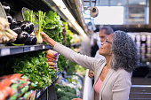 A senior couple pick out fresh produce together at the supermarket. The focus is on her as she reaches up to inspect veggies.