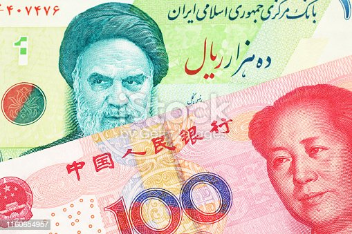 A close up image of a green Iranian ten thousand rial bank note with a red, one hundred yuan Chinese renminbi note in macro