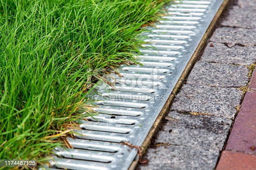 An iron gutter with grate to the drainage system on the side of the footpath paved with stone tiles and green lawn, close up.