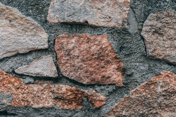 An irregular stone wall with different stones in closeup stock photo