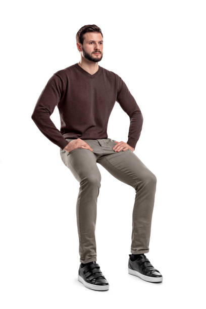An isolated bearded man in casual wear sits on a white background with hands on his thighs. An isolated bearded man in casual wear sits on a white background with hands on his thighs. Sitting and waiting. Meditating. Neutral expression. sitting stock pictures, royalty-free photos & images