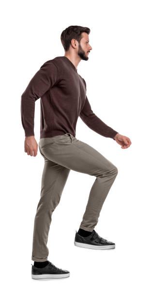 ein isolierte bärtiger mann in freizeitkleidung verstärkt mit einem bein in einer seitenansicht auf weißem hintergrund. - treppe stock-fotos und bilder
