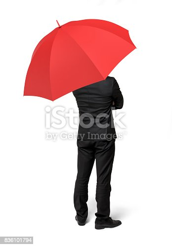 istock An isolated businessman standing with his back turned under a red umbrella 836101794