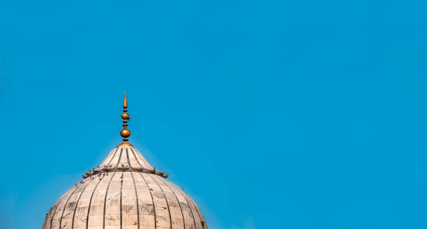 An isolated dome structure of mughal architecture with clear blue sky background as empty copy space for text. Design layout and template for Eid festival with a part of Jama Masjid mosque of Delhi. A white marble dome of the Jama Masjid, Delhi mosque isolated in blue sky, can be used as a background for travel guide, Eid festival greeting card and islamic religion concept. agra jama masjid mosque stock pictures, royalty-free photos & images