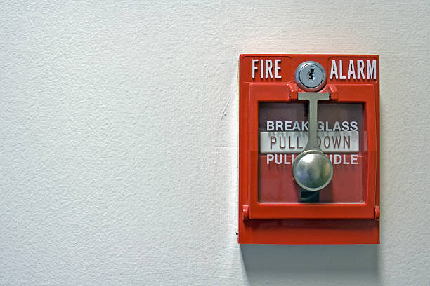 An isolated red fire alarm on a wall stock photo