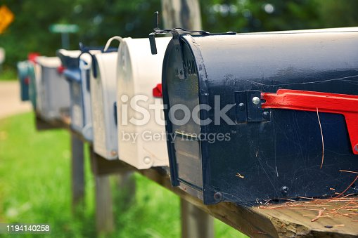 An isolated row of metal US mail boxes on wooden post in the countryside. Spider webs in one of them. Mail concept. New York City. United States.