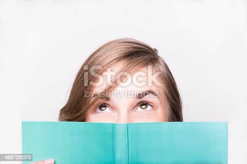 istock An isolated shot of a beautiful woman reading a book 488755070