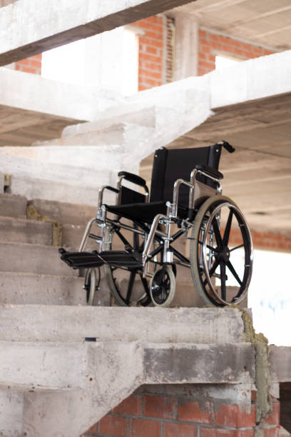 An isolated wheelchair in the middle of a stairway under construction stock photo